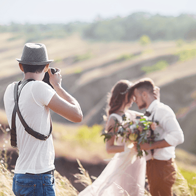 wedding photographer taking a picture on hillside